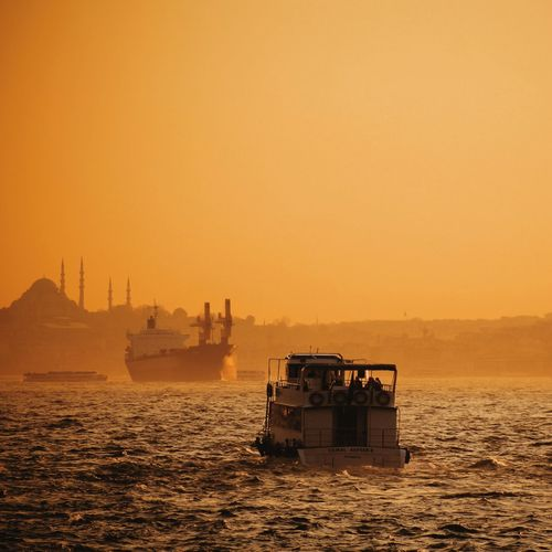 Boat sailing in sea against clear sky during sunset