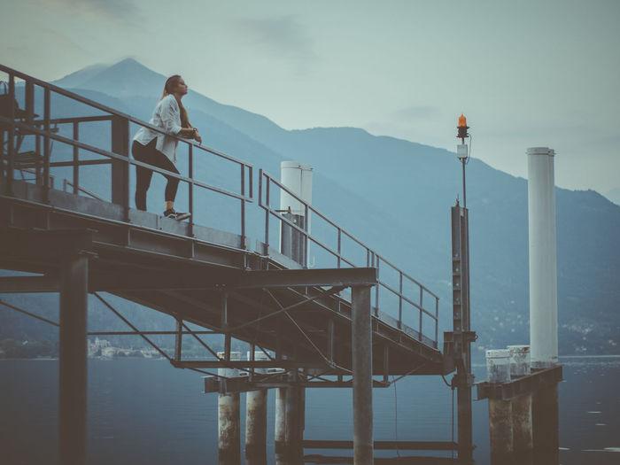 Man standing on railing by bridge against sky