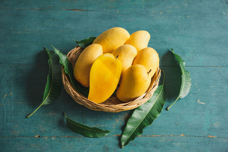 Mango in the basket Food Freshness Food And Drink Healthy Eating Wellbeing Fruit Table Leaf Still Life Plant Part Wood - Material Directly Above Basket No People Indoors  Yellow Green Color High Angle View Container Group Of Objects Leaves Ripe