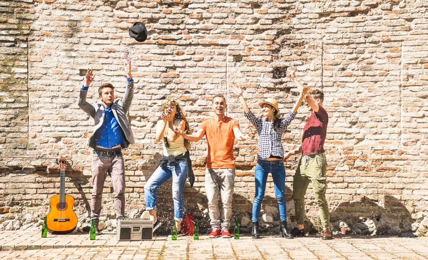 Cheerful friends throwing confetti while standing against brick wall