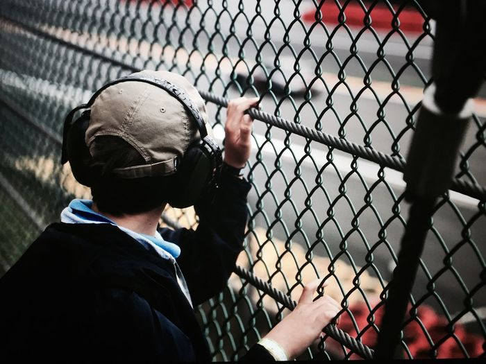 Rear View Of Man Wearing Headphones Standing At Fence