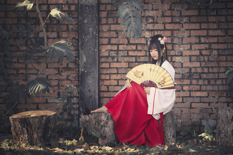 Young woman wearing traditional clothing while holding folding fan against brick wall