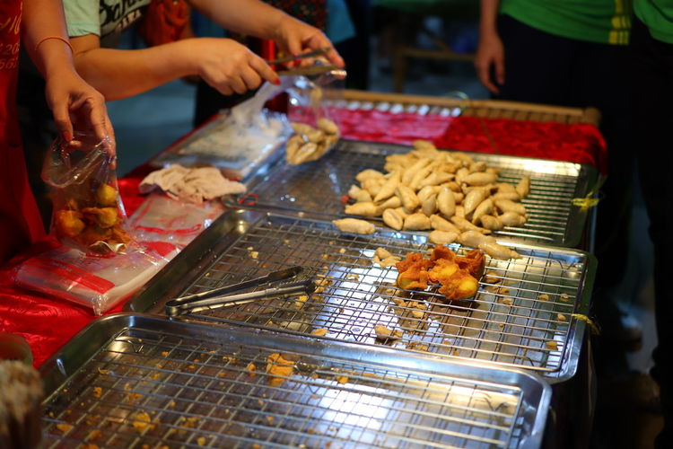 Person preparing food on barbecue grill at market