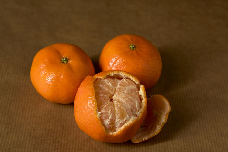 Close-up of three clementines on brown paper, with one half-peeled Citrus  ClementinesDay Freshness Brown Brown Paper Citrus Fruit Clementine Clementines Close Up Fruit Healthy Healthy Food Ingredient Mandarins Monochromatic Monochrome Mood Obst Orange Color Peel Peeling Pile Still Life Three