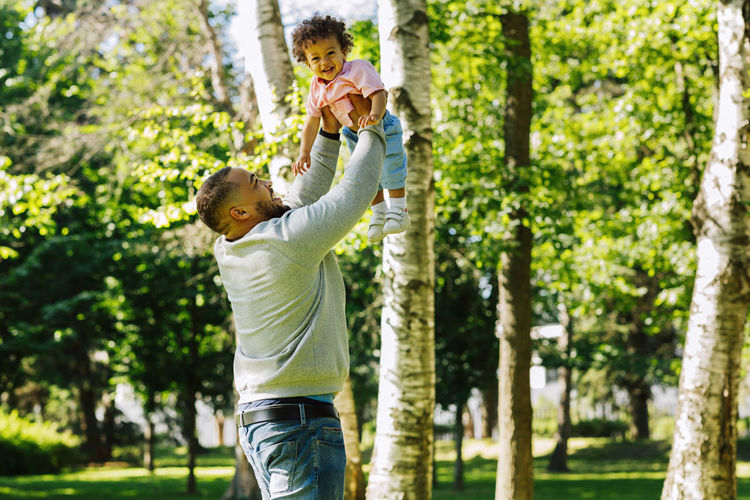 Man carrying happy toddler son at park