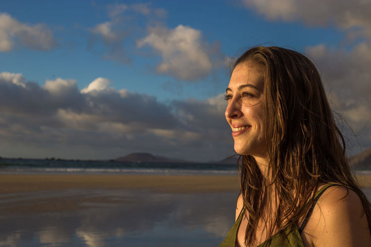 Portrait of smiling woman looking away against sky