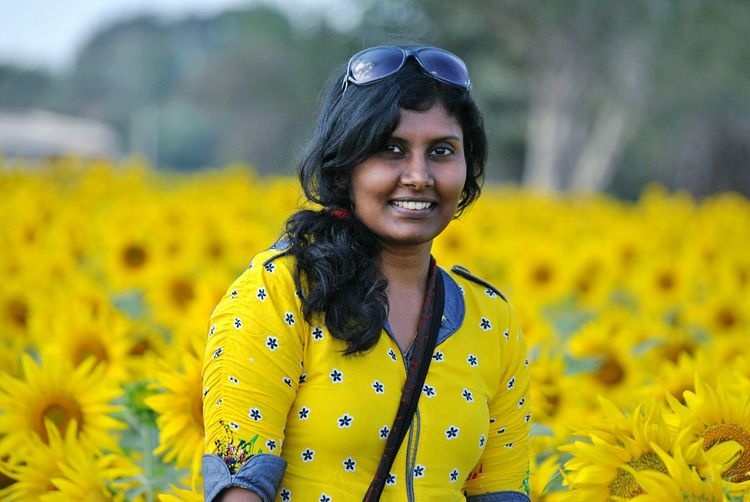 Portrait Of Woman Standing Against Yellow Flowers