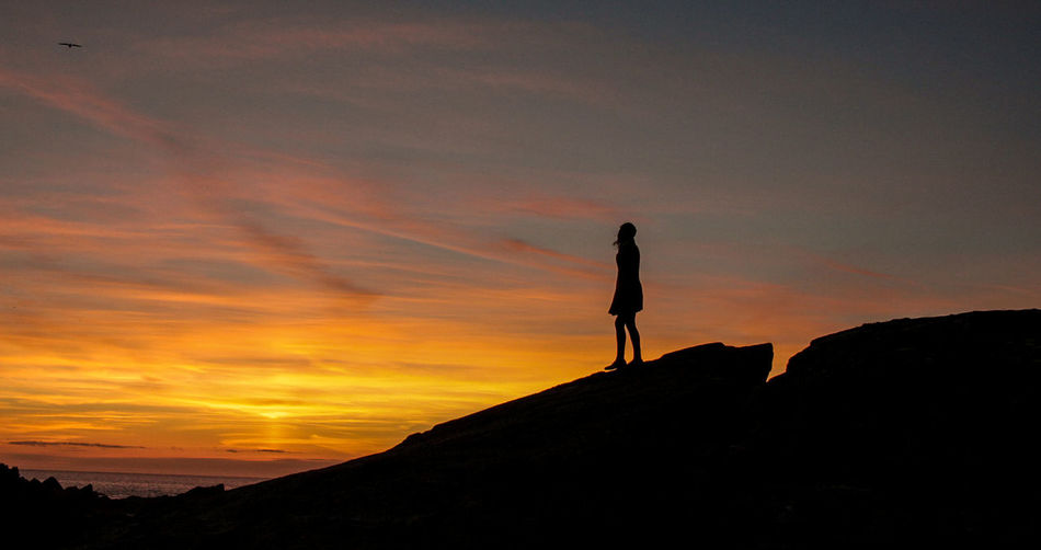 Silhouette woman standing on mountain against orange sky