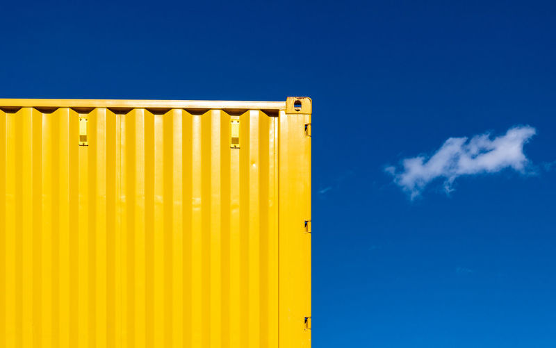 Yellow cargo container against blue sky