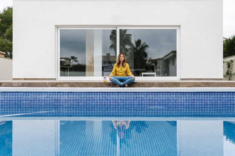Full length of woman sitting on swimming pool