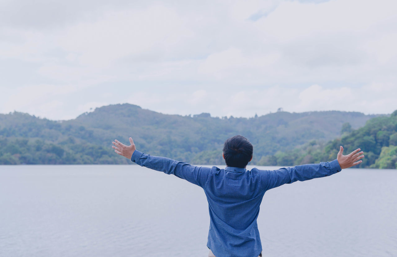 real people, arms outstretched, rear view, nature, gesturing, mountain, sky, arms raised, leisure activity, one person, lifestyles, beauty in nature, scenics, day, standing, outdoors, lake, men, human hand, people