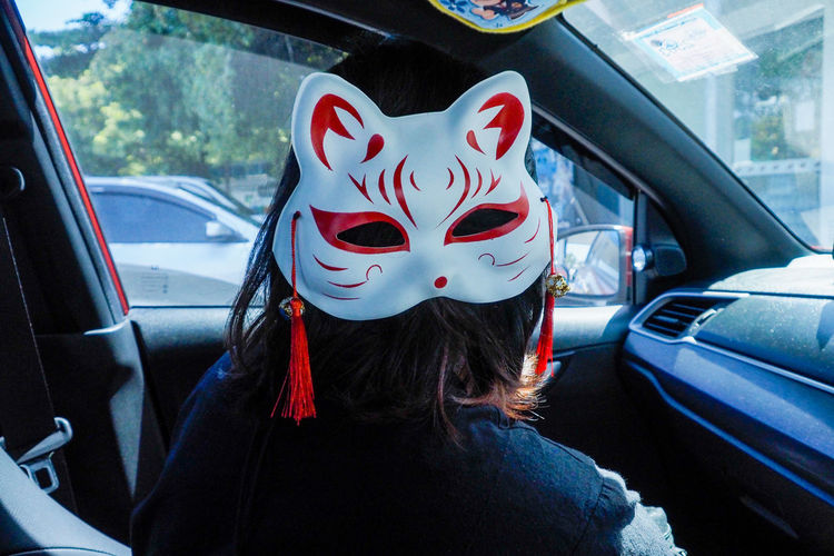 Woman wearing mask while sitting in car