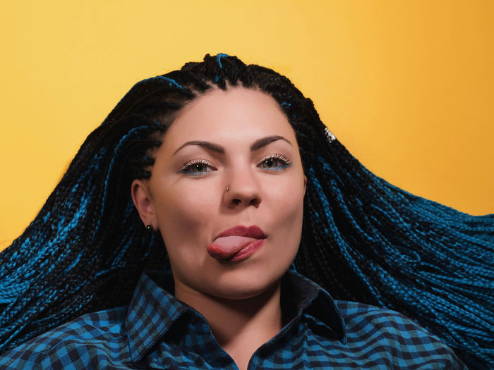 Portrait Of Young Woman With Braided Hair Sticking Out Tongue Against Yellow Background
