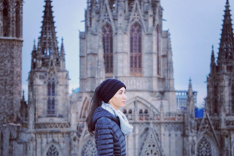 Woman Looking Away While Standing Against Cathedral