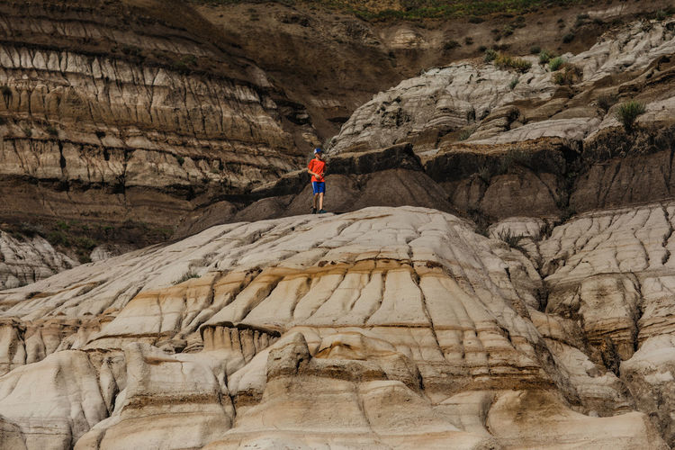 Rear view of person walking on rock