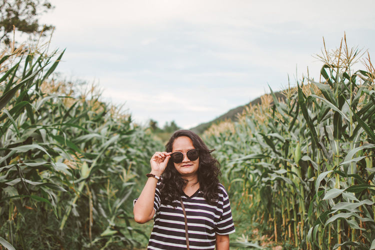 Portrait of mid adult woman wearing sunglasses while standing at farm