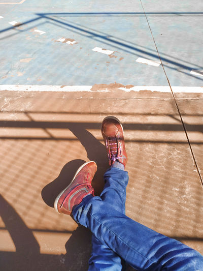 High angle view of a seated person's leg, wearing shoes