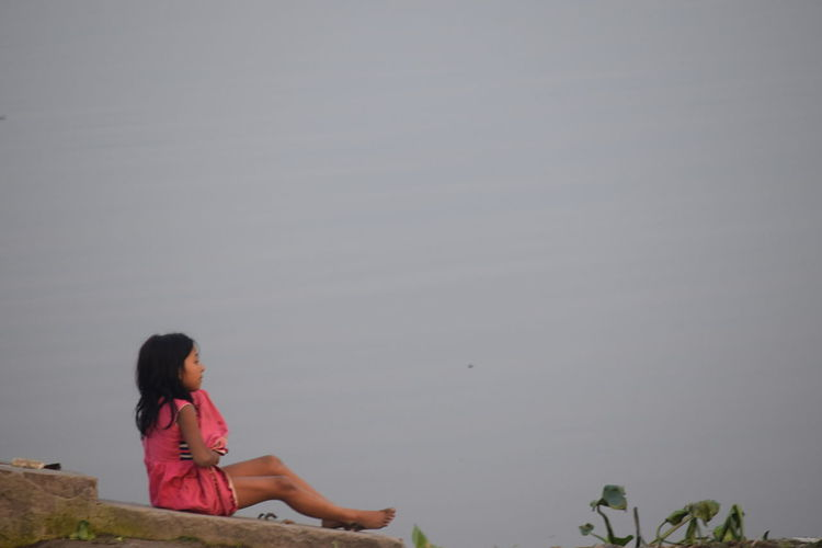 Girl Sitting On Rock By Lake