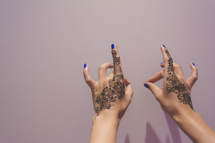 Cropped hands of woman with henna tattoo against purple background