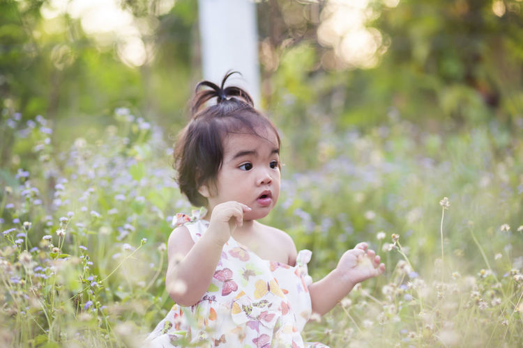 Portrait of cute girl with flowers against plants