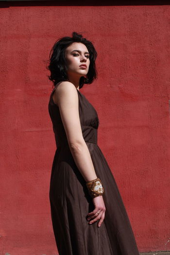 Beautiful woman in brown dress standing against red wall