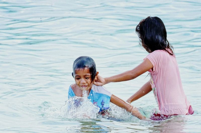 Siblings enjoying in lake