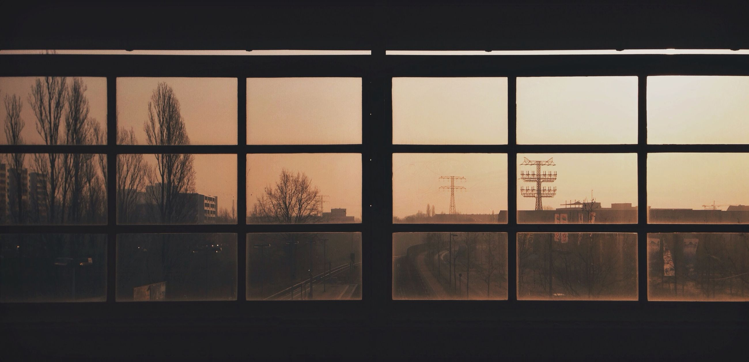 window, sunset, architecture, built structure, glass - material, building exterior, transparent, sky, indoors, tree, house, no people, silhouette, orange color, fence, city, residential structure, residential building, nature