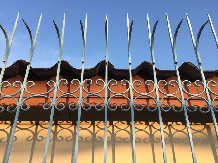 Close-up of metal fence against blue sky
