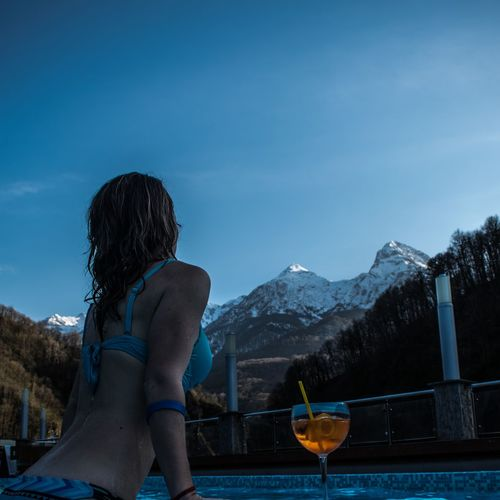 Side view of woman wearing bikini standing in swimming pool against clear blue sky