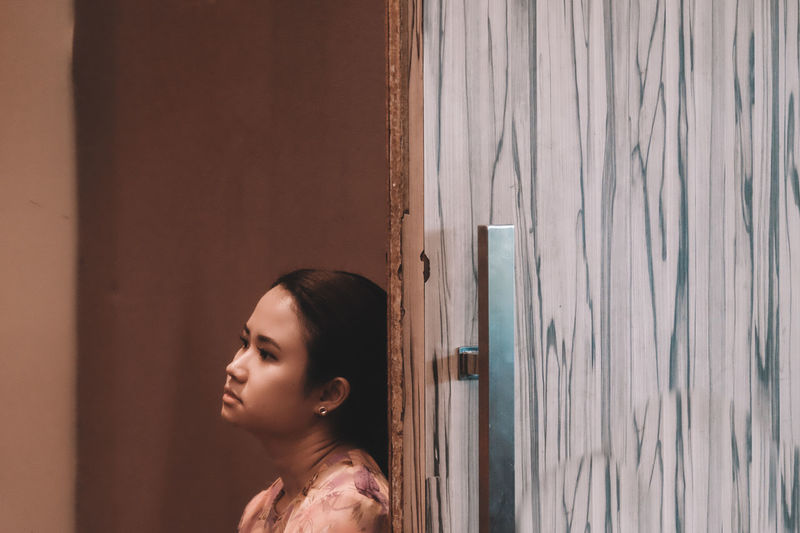 Thoughtful Woman Leaning On Wooden Door