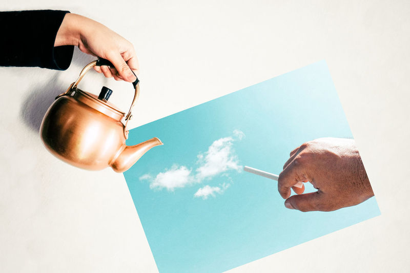 Optical illusion of hand holding tea kettle over photograph of man with cigarette emitting clouds