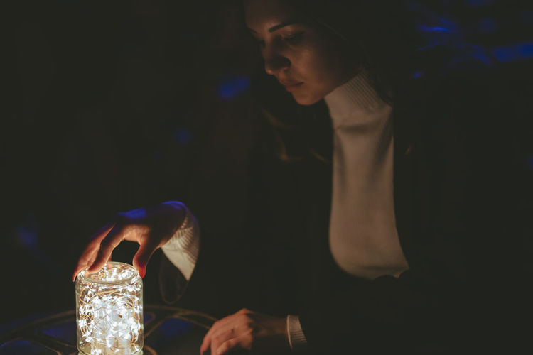 Woman holding jar with illuminated string light on table in darkroom