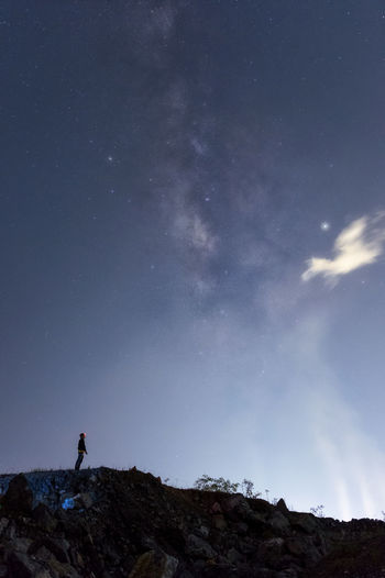 Silhouette man standing on mountain against sky at night