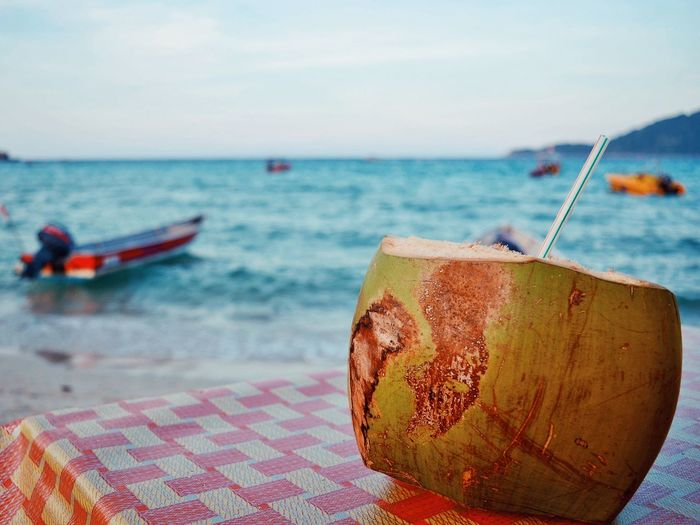 Close-up of coconut water on table at beach against sky