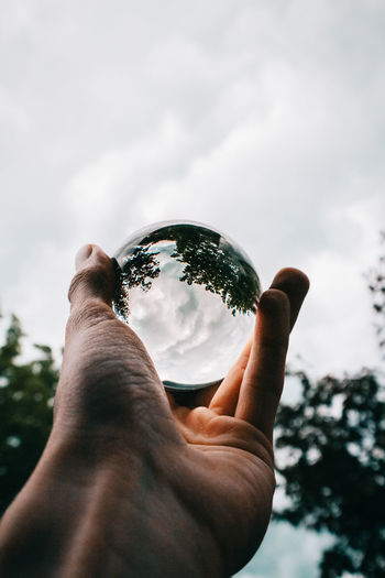 Close-Up Of Hand Holding Crystal Ball Against Cloudy Sky
