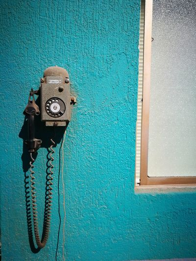 Close-up of old telephone on blue wall