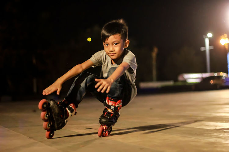 Boys Casual Clothing Child Childhood City Front View Full Length Innocence Leisure Activity Lifestyles Males  Men Night One Person Real People Sitting Sport Street
