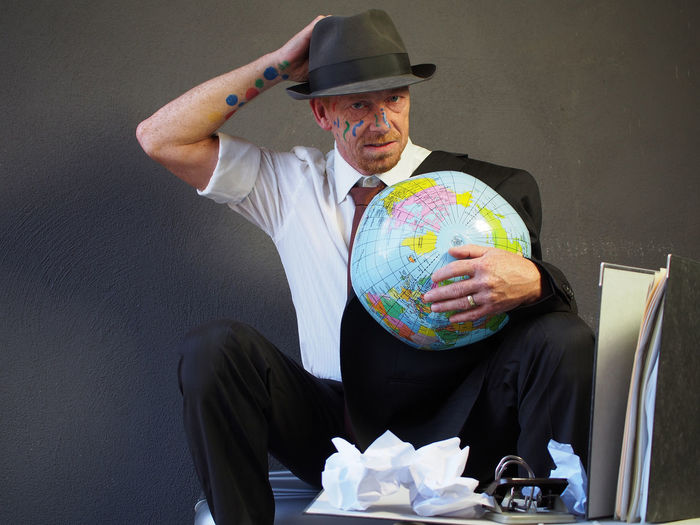 Portrait of businessman with face paint holding globe while standing at office