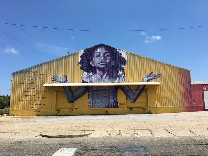 Graffiti on house in city against sky