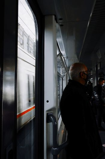 Side view of man standing at train