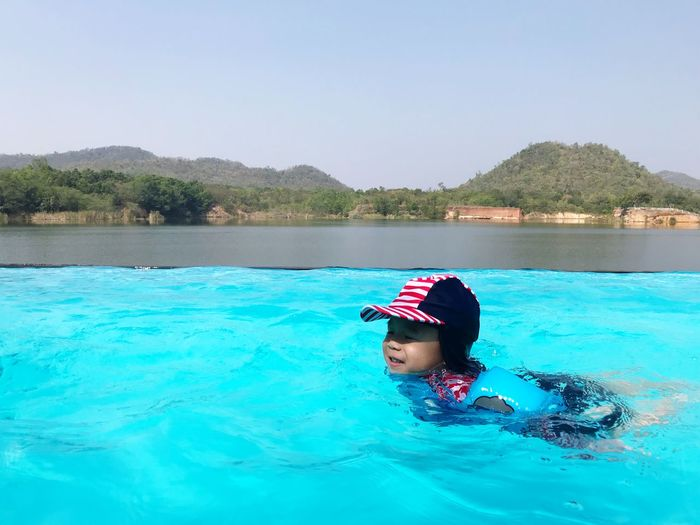 Boy swimming in infinity pool against clear sky