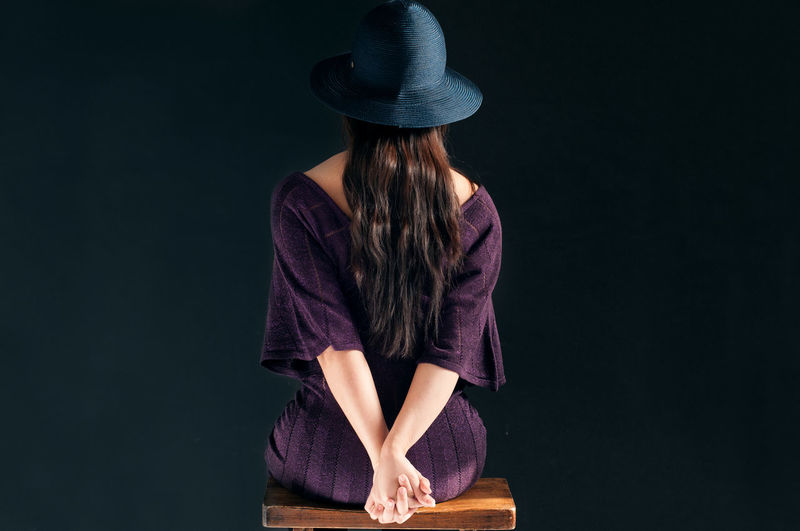 Rear view of young woman with hands clasped sitting on wooden stool against black background