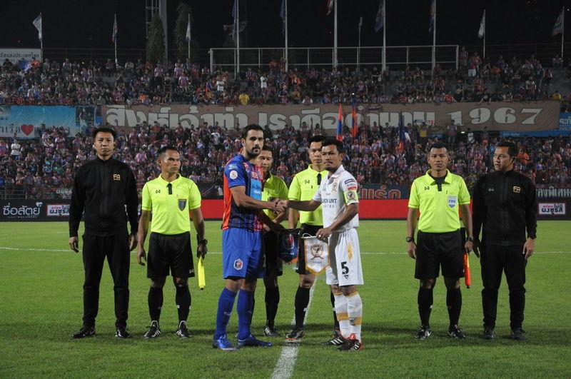 Full length of men standing on soccer field