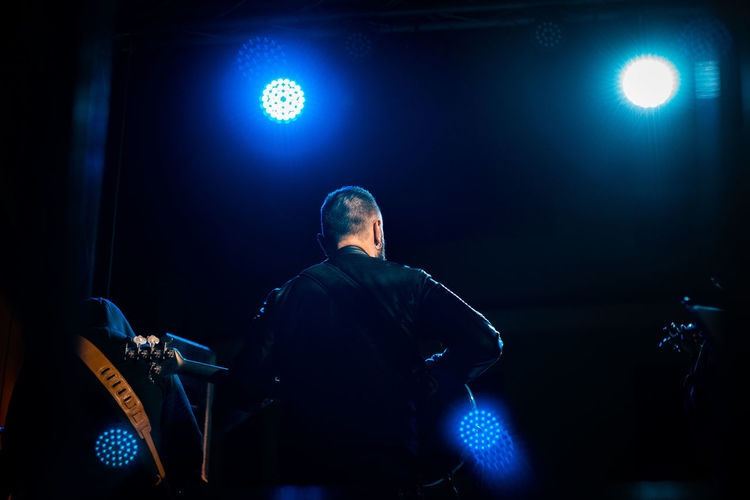 Rear view of man performing at music concert