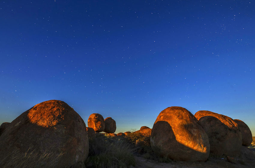 Dawn and stars over orange rocks Atmosphere Orange Rocks Astronomy Beauty In Nature Blue Blue Sky Clear Sky Day Devils Marbles Galaxy Landscape Nature No People Outdoors Rock - Object Rocks Sky Star - Space Stars