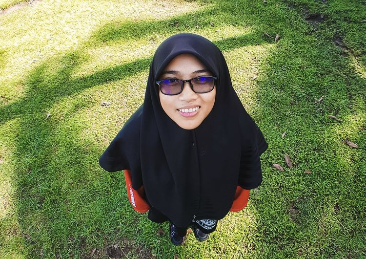 Portrait of smiling young woman wearing sunglasses on field