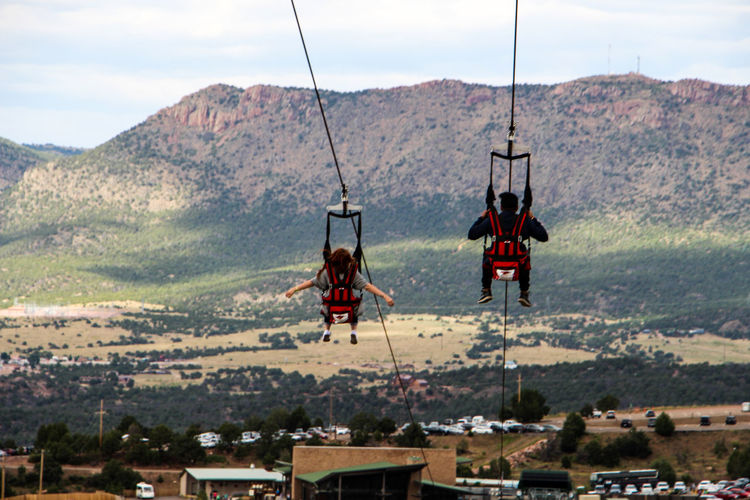Rear View Of People Zip Lines Against Mountain