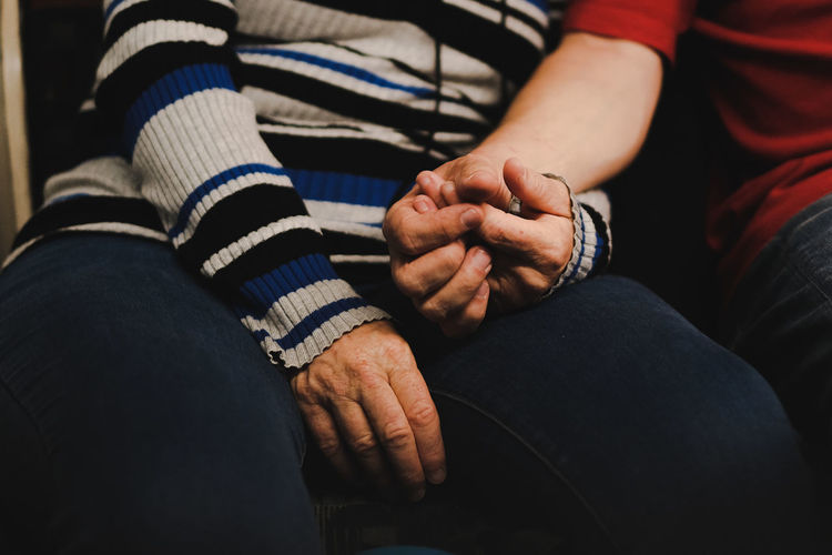 Midsection of man and woman holding hand sitting at home