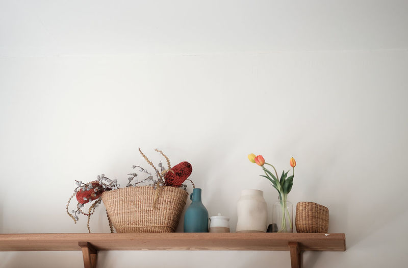 Potted plant in basket on table against wall