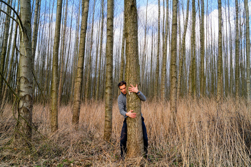 Man hugging tree trunk at forest